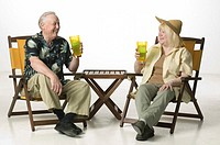 Couple with drinks, sitting in deckchairs, posing in studio, portrait