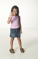 Young girl (6-7) standing in pose raising hand, portrait