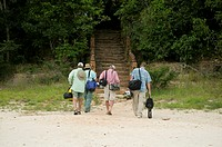 Four men walking to stairs from beach