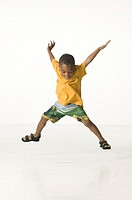 Young boy (4-5) doing star jump