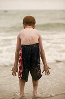 Boy (10-11) standing in surf, covered in sand, leaning forward, rear view