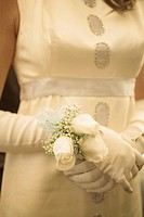 Teenage girl (14-16) in gown wearing corsage on wrist, mid section