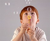 Boy (4-6) blowing bubbles through wand, close-up