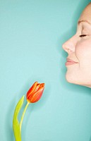 Young woman with tulip, side view