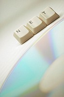 Close-up of computer keys near a CD spelling the word net