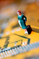 Close-up of the figurine of a woman with a briefcase on a circuit board