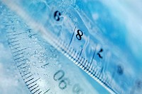 Close-up of a protractor and a ruler in water