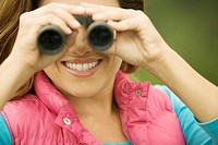 Close-up of a young woman looking through a pair of binoculars (thumbnail)