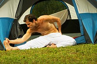 Close-up of a mid adult man exercising in front of a tent