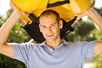 Portrait of a young man carrying a kayak on his head