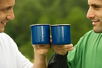 Close-up of a mid adult man and a mature man toasting with mugs