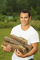 Portrait of a young man carrying firewood