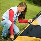 Side profile of a teenage girl putting up a tent