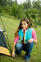 Portrait of a teenage girl crouching besides a tent