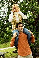 Mid adult man carrying a young woman on his shoulders