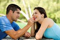 Side profile of a mid adult man feeding a young woman a strawberry