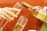 Close-up of a person's hand pouring champagne