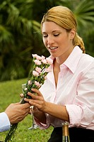 Close-up of a man giving a bunch of flowers to a businesswoman