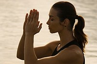 Side profile of a young woman meditating in a lake