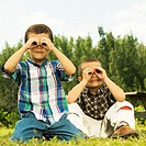 Close-up of two boys looking through their hands