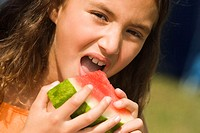Portrait of a girl eating a slice of a watermelon