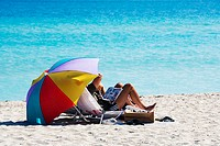 Two people under a beach umbrella, Miami, Florida, USA