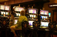 Rear view of a man sitting at a slot machine, New Orleans, Louisiana, USA