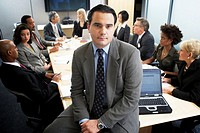 Businessman sitting on table in meeting, portrait