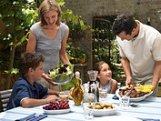 Parents with children (9-12) bringing food to table outdoors