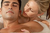 Close-up of a young woman looking at a young man in a bathtub