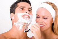 Close-up of a young woman shaving a mid adult man´s face