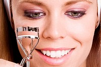 Close-up of a young woman using an eyelash curler