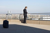 Businessman standing on roof of building, looking at mobile phone