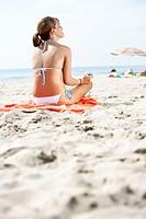 Young woman wearing bikini, sitting on beach, rear view