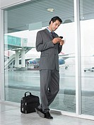 Businessman using palm top in airport, low angle view