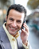 Businessman using mobile phone, smiling, close up, portrait
