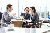 Three businesspeople sat at table outdoors, smiling