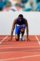 Male Runner Crouched On Starting Blocks