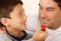 Close-up of a boy feeding his father a strawberry