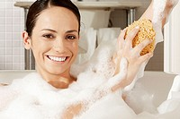 Portrait of a young woman using a bath sponge on her arm