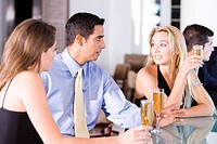 Two young women and a mid adult man sitting at a bar counter