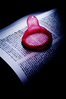 Red colour condom on an opened dictionary
