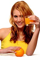 A woman touching an orange on the table while holding up a glass of orange juice