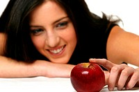 A woman resting her chin on her right hand while her left hand touching a red apple