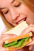 A blonde hair girl eating a sandwich