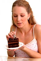 A woman using a fork to cut a chocolate cake