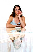 A woman posing with a muffin on the table