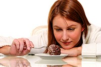 A woman looking down with her chin on her hand while using a fork to poke a chocolate ball cake