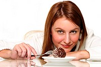 A woman resting her chin on her hand while using a fork to poke a chocolate ball cake