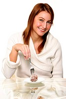 A woman using a fork to eat a chocolate ball cake